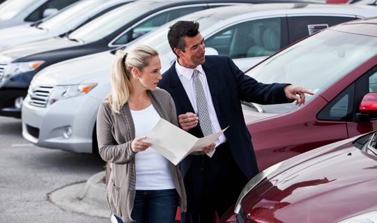 Woman shopping for a new car, talking to a car salesman.